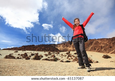 Happy hiking with arms in the air. Woman hiker excited and cheerful traveling on Teide, Tenerife, Canary Islands.