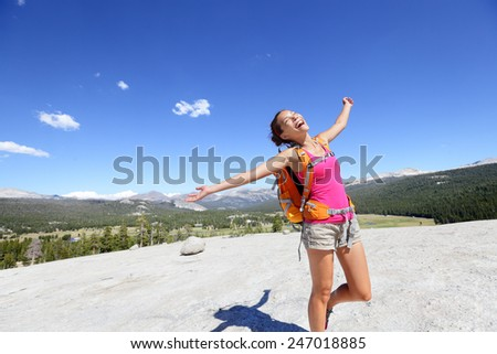 Happy hiking woman dancing in mountain landscape. Young asian adult doing funny freedom pose on top of the Pothole Dome in Yosemite National Park, California, USA. - stock photo