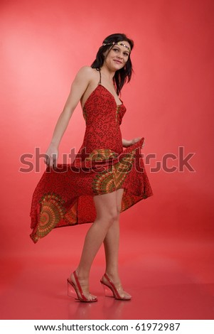 Happy hippie girl dancing in studio on red background