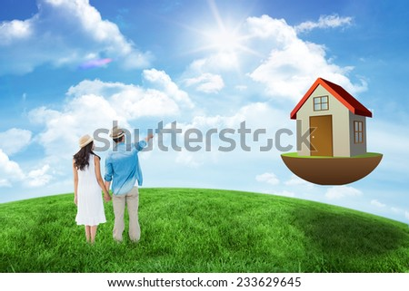 Happy hipster couple holding hands and looking against green hill under blue sky - stock photo