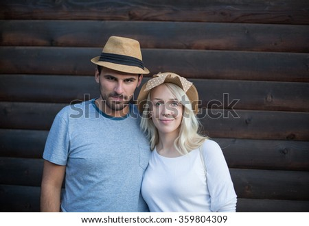 Happy hipster couple hugging and smiling against wooden planks