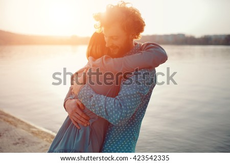 Happy hipster couple on holiday having fun and enjoy the time. Couple in love kissing and hugging each other by the lake - stock photo