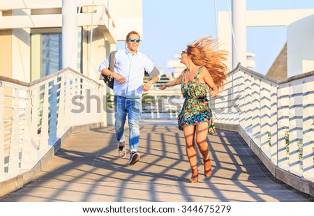 Happy hipster couple on holiday having fun and enjoy the time together. Dating young best friends in love enjoying life moments and running on bridge. Guys in city looking each other and flirting - stock photo