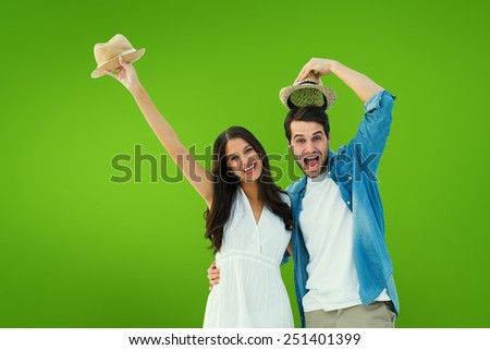 Happy hipster couple smiling at camera and cheering against green vignette - stock photo