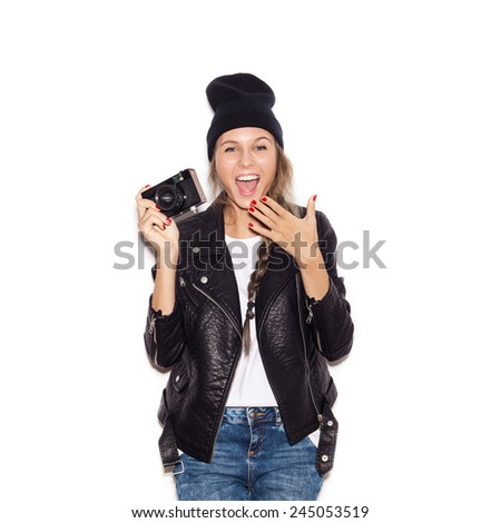 Happy hipster girl in black beanie having fun with vintage noname camera. Laughing young woman. White background, not isolated - stock photo