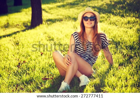 Happy Hipster Girl Relaxing on the Grass. Toned and Filtered Photo. Modern Youth Lifestyle Concept. - stock photo