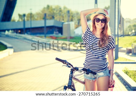 Happy Hipster Girl with Bike in the City. Toned and Filtered Photo. Modern Youth Lifestyle Concept. - stock photo