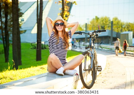 Happy Hipster Girl with Her Bike in the City