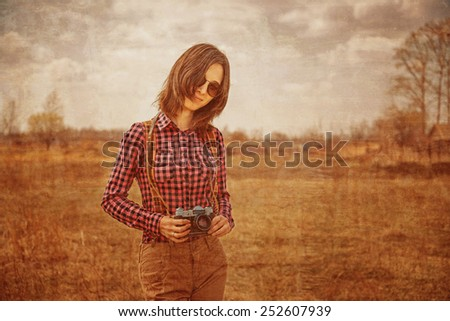 Happy hipster girl with vintage photo camera on nature. Vintage image. - stock photo