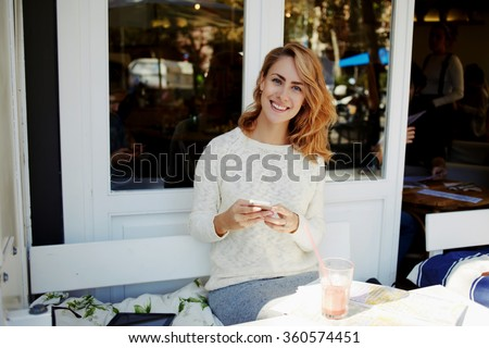Happy hipster girl writing text messaging on cell telephone during recreation time in cozy coffee shop, young woman tourist viewing map of the city on mobile phone while sitting in sidewalk cafe  - stock photo
