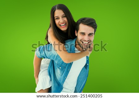 Happy hipster giving his girlfriend a piggy back against green vignette - stock photo