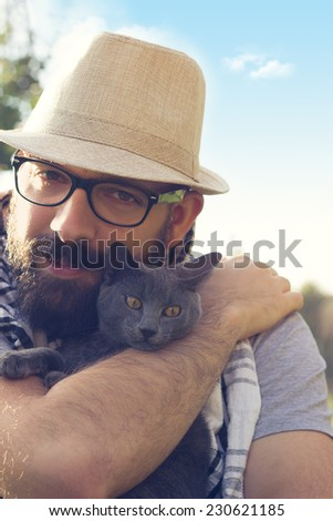 Happy hipster hugging his Russian Blue cat