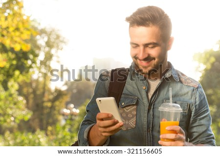 Happy hipster man using mobile phone and drinking orange cocktail. Handsome man spending his daytime walking in the park. - stock photo