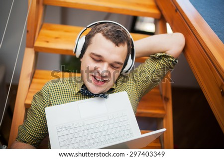 Happy hipster relaxing at home. He listening to music in headphones or watching movie using laptop while lying on wooden stairs - stock photo