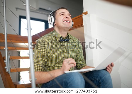 Happy hipster style man listening to music in wireless earphones and using laptop while sitting on the wooden stairs at home - stock photo
