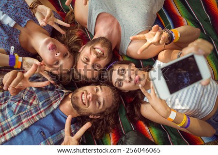 Happy hipsters posing for selfie at a music festival - stock photo