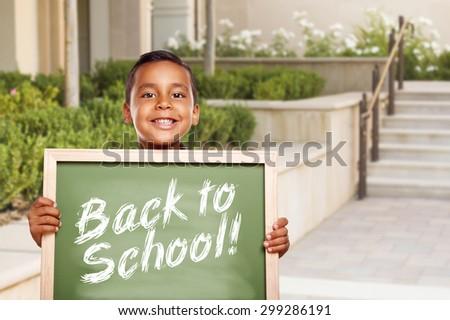 Happy Hispanic Boy Holding Back to School Chalk Board Outside on School Campus. - stock photo