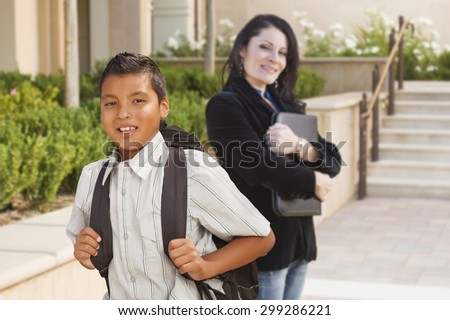 Happy Hispanic Boy with Backpack on School Campus and Teacher Behind.