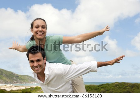 happy hispanic couple in love, man giving piggyback to woman - stock photo