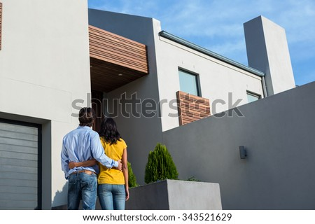 Happy Hispanic couple standing and looking at the new house - stock photo