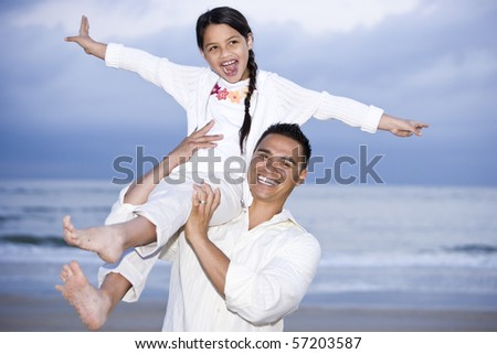 Happy Hispanic dad and 9 year old daughter having fun on beach - stock photo