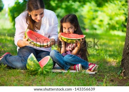 Happy hispanic family eating watermelon at park - stock photo
