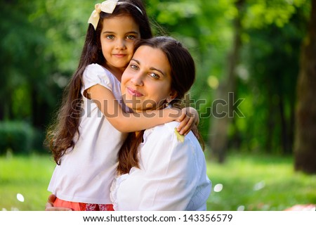Happy hispanic family playing in sunny park - stock photo