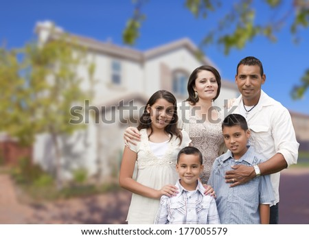 Happy Hispanic Family Portrait in Front of Beautiful House. - stock photo