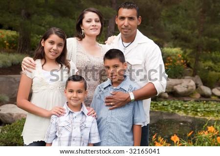 Happy Hispanic Family Portrait In the Park. - stock photo
