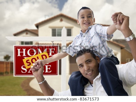Happy Hispanic Father and Son in Front of New House and Sold Real Estate Sign. - stock photo