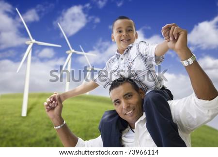 Happy Hispanic Father and Son with Wind Turbine Farm Over Blue Sky. - stock photo