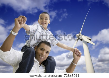 Happy Hispanic Father and Son with Wind Turbine Over Blue Sky. - stock photo