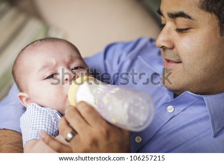 Happy Hispanic Father Bottle Feeding His Very Content Son. - stock photo