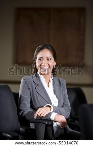 Happy Hispanic female office worker in office boardroom - stock photo