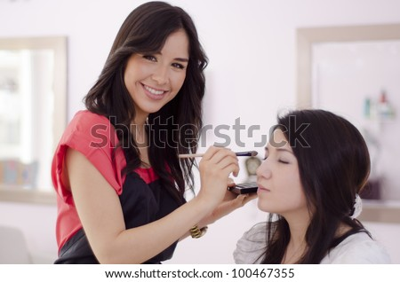 Happy hispanic makeup artist applying makeup on a client - stock photo