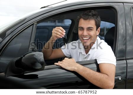 Happy hispanic man showing the key of his new car - stock photo