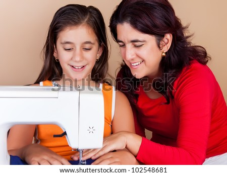 Happy hispanic mother teaching her daughter how to use a sewing machine - stock photo