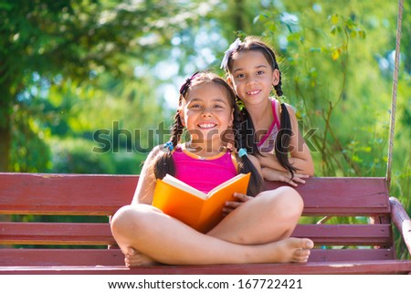 Happy hispanic sisters reading book in summer park - stock photo