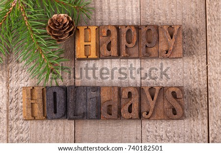 Happy holidays text on a wooden surface with evergreen tree branch and pinecone