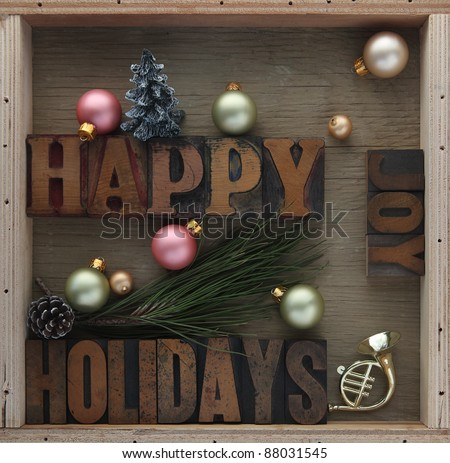 happy holidays words with ornaments, pine cone, toy horn and Christmas tree - stock photo