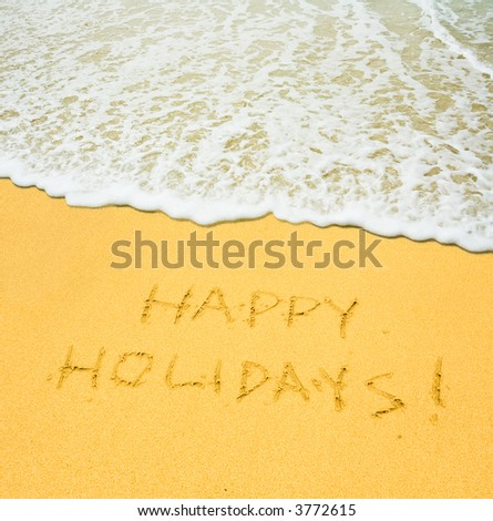 happy holidays written in the sandy beach - stock photo