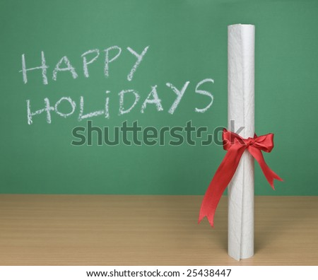 Happy holidays written on a chalkboard with a diploma on forefround. - stock photo
