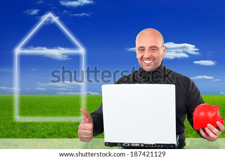 Happy home-builder doing online-banking with a piggybank in his hand