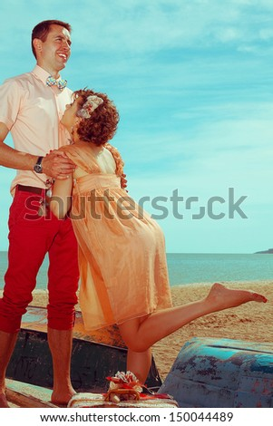 Happy honeymoon (vacation) concept. Young married couple of hipsters in trendy clothes standing on a boat, playing and laughing. Sunny summer day, blue sky. Copy-space. Outdoor shot