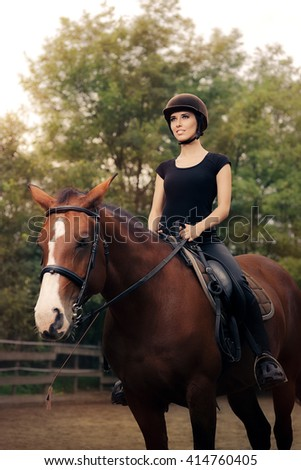 Happy Horsewoman ridding  in a Manege - Cute girl wearing a safety helmet practicing riding