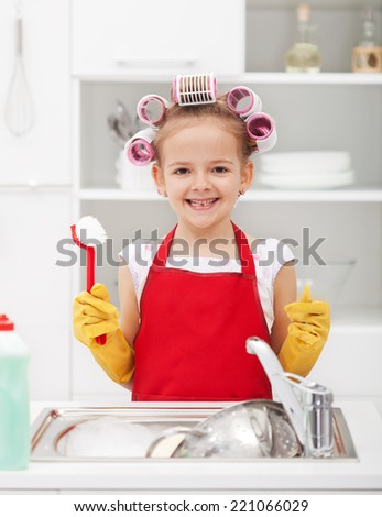Happy housekeeping fairy - washing the dishes with a grin - stock photo
