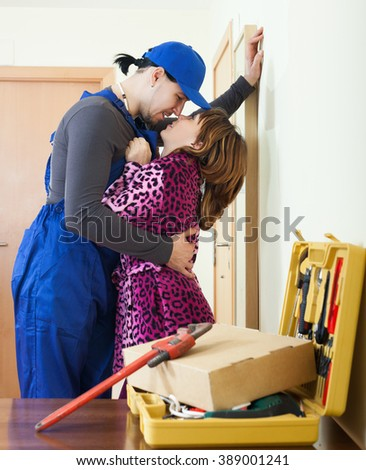 happy housewife having flirt with service worker at home