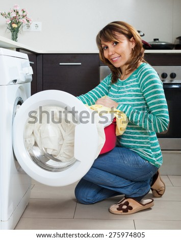 Happy housewife in green using washing machine at home - stock photo