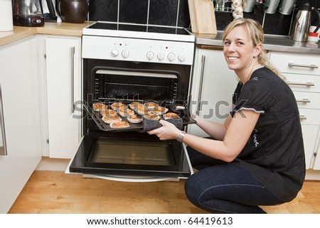 Happy housewife in the kitchen - stock photo