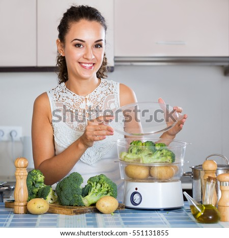 Happy housewife on diet cooking vegetables in the steamer indoors